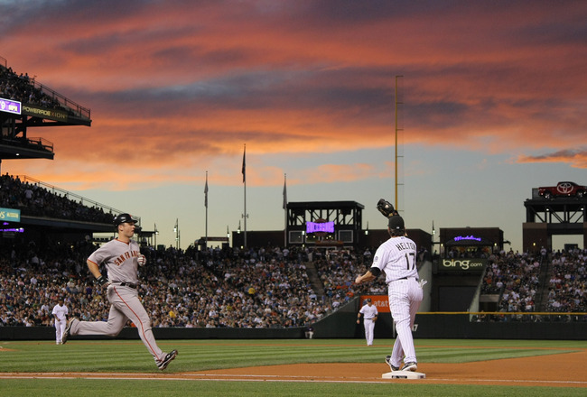 DENVER - SEPTEMBER 24:  First baseman Todd Helton #17 of the Colorado Rockies gets the put out on Buster Posey of the San Francisco Giants as he grounds out as the sun sets in the fourth inning at Coors Field on September 24, 2010 in Denver, Colorado. The