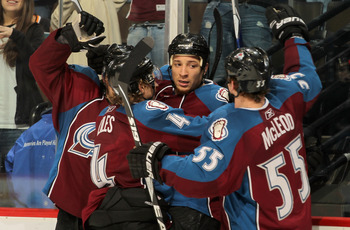 DENVER - NOVEMBER 17:  Chris Stewart #25 (C) of the Colorado Avalanche celebrates his third period goal against the San Jose Sharks John-Michael Liles #4 and Cody McLeod #55 at the Pepsi Center on November 17, 2010 in Denver, Colorado. The Avalanche defea