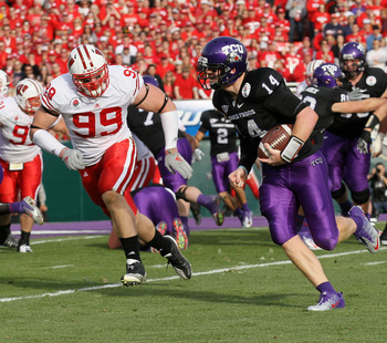 PASADENA, CA - JANUARY 01:  Quarterback Andy Dalton #14 of the TCU Horned Frogs rushes with the ball as J.J. Watt #99 of the Wisconsin Badgers runs after him in the first quarter of the 97th Rose Bowl game on January 1, 2011 in Pasadena, California.  (Pho