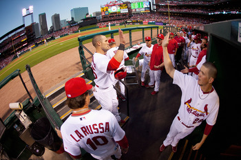 ST. LOUIS - SEPTEMBER 3: Skip Schumaker #55 of the St. Louis Cardinals is congratulated by teammates after scoring a run against the Cincinnati Reds at Busch Stadium on September 3, 2010 in St. Louis, Missouri.  The Cardinals beat the Reds 3-2.  (Photo by