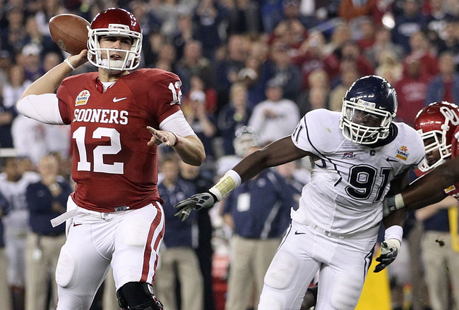 GLENDALE, AZ - JANUARY 01:  Landry Jones #12 of the Oklahoma Sooners passes the ball as Jesse Joseph #91 of the Connecticut Huskies rushes in past Donald Stephenson #59 of the Sooners in the first half against the Connecticut Huskies during the Tostitos F