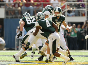 ORLANDO, FL - JANUARY 01:  Kirk Cousins #8 of the Michigan State Spartans hands the ball off to Edwin Baker #4 during the Capitol One Bowl against the Alabama Crimson Tide at the Florida Citrus Bowl on January 1, 2011 in Orlando, Florida.  (Photo by Mike