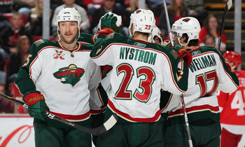 DETROIT, MI - NOVEMBER 19:  Cam Barker #25 and his teamamtes on the Minnesota Wild celebrate a goal in a game against the Detroit Red Wings on November 19, 2010 at the Joe Louis Arena in Detroit, Michigan. The Wild defeated the Wings 4-3 in overtime. (Pho
