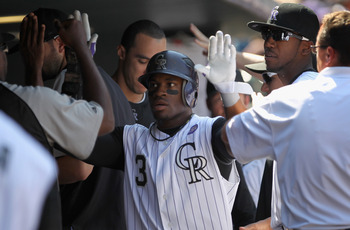DENVER - SEPTEMBER 15:  Eric Young Jr #3 of the Colorado Rockies is welcomed back to the dugout after he scored on a single by Troy Tulowitzki off of starting pitcher Clayton Richard of the San Diego Padres to give the Rockies a 1-0 lead in the first inni