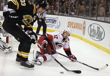 BOSTON - NOVEMBER 26:  Zdeno Chara #33 of the Boston Bruins takes the puck from Eric Staal #12 of the Carolina Hurricanes on November 26, 2010 at the TD Garden in Boston, Massachusetts.  (Photo by Elsa/Getty Images)