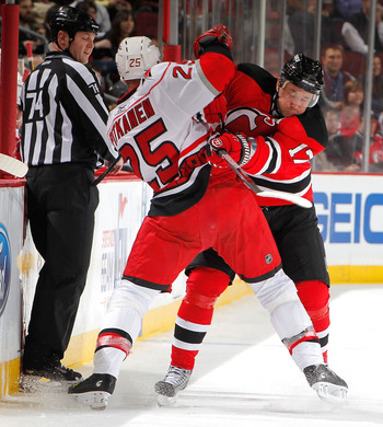 NEWARK, NJ - FEBRUARY 08:  Joni Pitkanen #25 of the Carolina Hurricanes is checked by Ilya Kovalchuk #17 of the New Jersey Devils during the second period of an NHL hockey game at the Prudential Center on February 8, 2011 in Newark, New Jersey.  (Photo by