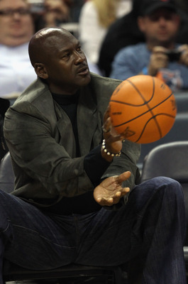 CHARLOTTE, NC - NOVEMBER 08:  Michael Jordan, owner of the Charlotte Bobcats, throws the ball back to an official during their game against the San Antonio Spurs at Time Warner Cable Arena on November 8, 2010 in Charlotte, North Carolina.  NOTE TO USER: U