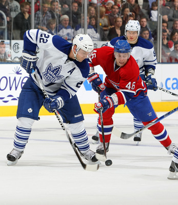 TORONTO - DECEMBER 11:  Francois Beauchemin #22 of the Toronto Maple Leafs battles for the puck with Andrei Kostitsyn #46 of the Montreal Canadiens during their NHL game at Air Canada Centre on December 11, 2010 in Toronto, Ontario, Canada.(Photo By Dave