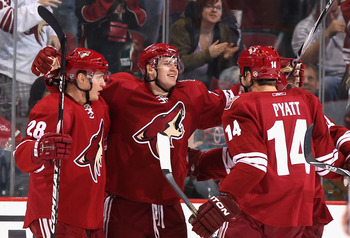 GLENDALE, AZ - JANUARY 17:  Oliver Ekman-Larsson #23 of the Phoenix Coyotes celebrates with teammates Lauri Korpikoski #28 and Taylor Pyatt #14 after Ekman-Larsson scored his first career goal against the San Jose Sharks during the third period of the NHL