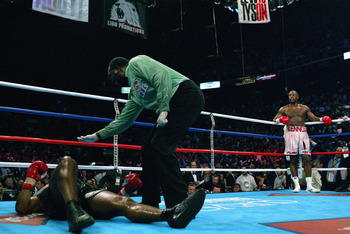MEMPHIS, TN - JUNE 8:  Mike Tyson is counted out as Lennox Lewis patiently waits in his corner during their WBC/IBF heavyweight championship bout on June 8, 2002 at The Pyramid in Memphis, Tennessee.  Lewis won the bout by way of knockout in the 8th round