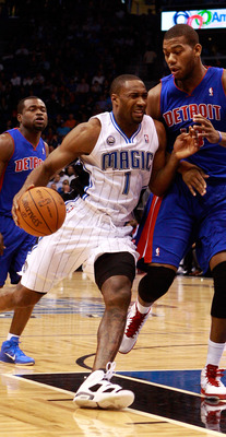 ORLANDO, FL - JANUARY 24:  Gilbert Arenas #1 of the Orlando Magic drives against Greg Monroe #10 of the Detroit Pistons during the game at Amway Arena on January 24, 2011 in Orlando, Florida.  NOTE TO USER: User expressly acknowledges and agrees that, by