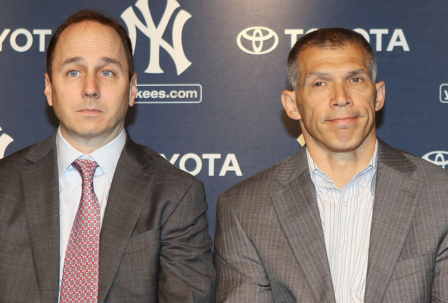 NEW YORK, NY - JANUARY 19:  General manager Brian Cashman (L) and manager Joe Girardi of the New York Yankees listen as Rafael Soriano (not pictured) speaks during his introduction press conference on January 19, 2011 at Yankee Stadium in the Bronx boroug