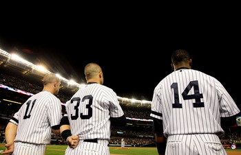NEW YORK - OCTOBER 18:  (L-R) Brett Gardner #11, Nick Swisher #33 and Curtis Granderson #14 of the New York Yankees stand for the performance of 'God Bless America'  against the Texas Rangers in Game Three of the ALCS during the 2010 MLB Playoffs at Yanke