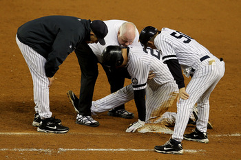 NEW YORK - OCTOBER 19:  Mark Teixeira #25 of the New York Yankees is tended to by Manager Joe Girardi after hurting himself as first base coach Mick Kelleher #50 looks on while playing against the Texas Rangers in Game Four of the ALCS during the 2010 MLB