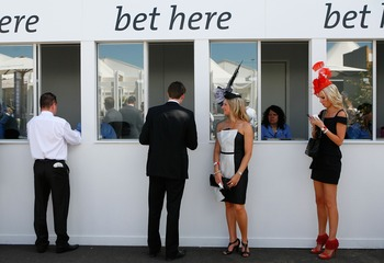 MELBOURNE, AUSTRALIA - OCTOBER 31:  Racegoers place a bet during the AAMI Victoria Derby Day at Flemington Racecourse on October 31, 2009 in Melbourne, Australia.  (Photo by Scott Barbour/Getty Images)