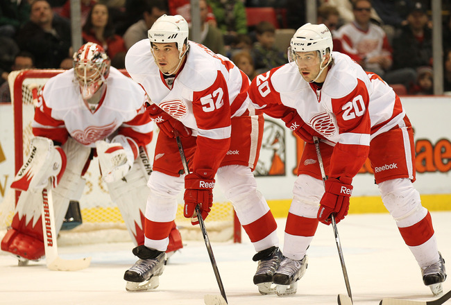DETROIT, MI - JANUARY 22:  Jonathan Ericsson #52 and Drew Miller #20 of the Detroit Red Wings wait for a faceoff in a game against the Chicago Black Hawks on January 22, 2011 at the Joe Louis Arena in Detroit, Michigan. The Hawks defeated the Wings 4-1. (