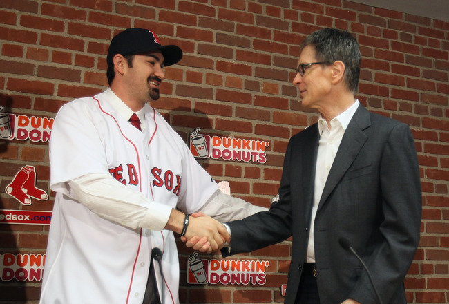 BOSTON, MA - DECEMBER 06:  Adrian Gonzalez (L) shakes hands with principle owner John Henry during a press conference announcing that he signed with the Boston Red Sox on December 6,  2010 at Fenway Park in Boston, Massachusetts.  (Photo by Elsa/Getty Ima