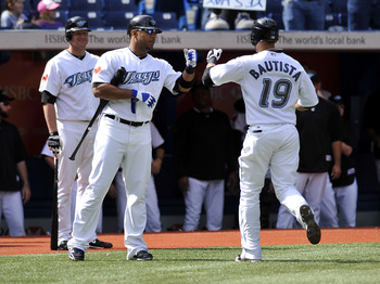 TORONTO - SEPTEMBER 23:   Jose Bautista # 19 of the Toronto Blue Jays high fives teammate Vernon Wells #10 after hitting his 50th home run of the season during the game against the Seattle Mariners on September 23, 2010 at Rogers Centre in Toronto, Ontari