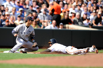 BALTIMORE - SEPTEMBER 19:  Brian Roberts #1 of the Baltimore Orioles slides safely into third base ahead of the tag of Ramiro Pena #19 of the New York Yankees at Camden Yards on September 19, 2010 in Baltimore, Maryland.  (Photo by Greg Fiume/Getty Images