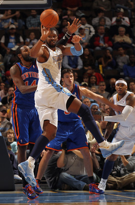 DENVER - NOVEMBER 16:  Nene #31 of the Denver Nuggets passes the ball while under defensive pressure from Ronny Turiaf #14 of the New York Knicks at the Pepsi Center on November 16, 2010 in Denver, Colorado. NOTE TO USER: User expressly acknowledges and a