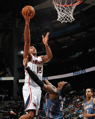 ATLANTA, GA - FEBRUARY 12:  Al Horford #15 of the Atlanta Hawks drives against Gerald Wallace #3 of the Charlotte Bobcats at Philips Arena on February 12, 2011 in Atlanta, Georgia.  NOTE TO USER: User expressly acknowledges and agrees that, by downloading