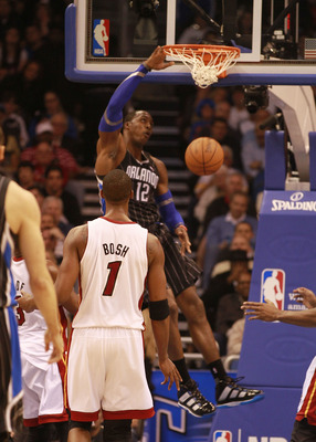 ORLANDO, FL - FEBRUARY 03:  Center Dwight Howard #12 of the Orlando Magic dunks against the Miami Heat at Amway Arena on February 3, 2011 in Orlando, Florida. NOTE TO USER: User expressly acknowledges and agrees that, by downloading and/or using this Phot