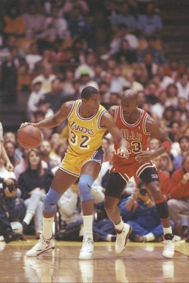 3 Feb 1991: Guard Erving Johnson of the Los Angeles Lakers dribbles the ball as guard Michael Jordan of the Chicago Bulls defends him during a game at the Great Western Forum in Inglewood, California.