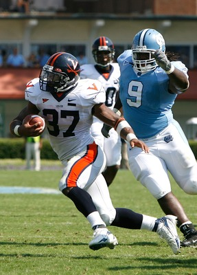 CHAPEL HILL, NC - SEPTEMBER 15:  Tailback Cedric Peerman #37 of the Virginia Cavaliers rushes away from defensive tackle Marvin Austin #9 of the North Carolina Tar Heels during the Cavaliers 22-20 win in their Atlantic Coast Conference football game at Ke
