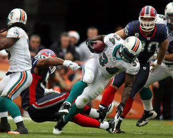 MIAMI, FL - DECEMBER 19:  Running back Ricky Williams #34 of the Miami Dolphins is upended by cornerback Donte Whitner #20 of the Buffalo Bills during a game at Sun Life Stadium on December 19, 2010 in Miami, Florida. The Bills defeated the Dolphins 17-14