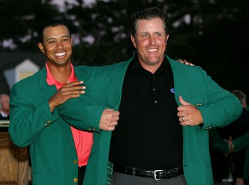 AUGUSTA, GA - APRIL 09:  Tiger Woods puts the green jacket on Phil Mickelson after he won The Masters at the Augusta National Golf Club after the final round on April 9, 2006 in Augusta, Georgia.   Mickelson won with the score seven under.  (Photo by Davi