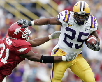 BATON ROUGE, LA - NOVEMBER 25:  Justin Vincent #25 of Louisiana State University avoids a tackle by Vickiel Vaughn #31 of the University of Arkansas on November 25, 2005 at Tiger Stadium in Baton Rouge, Louisiana.  (Photo by Chris Graythen/Getty Images)
