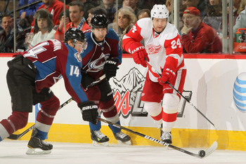 DENVER, CO - JANUARY 10:  Ruslan Salei #24 of the Detroit Red Wings passes the puck past Tomas Fleischmann #14 of the Colorado Avalanche at the Pepsi Center on January 10, 2011 in Denver, Colorado.  (Photo by Doug Pensinger/Getty Images)
