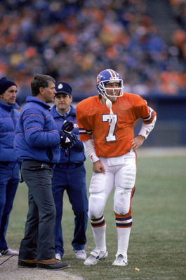 DENVER - DECEMBER 8:  Head coach Dan Reeves talks with quarterback John Elway #7 of the Denver Broncos on the sidelines during a game against the Los Angeles Raiders at Mile High Stadium on December 8, 1985 in Denver, Colorado.  The Raiders won 17-14 in o