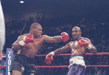 28 Jun 1997: Mike Tyson misses with a left as Evander Holyfield steps aside during their heavyweight title fight at the MGM Grand Garden in Las Vegas, Nevada. Holyfield won the fight when referee Mills Lane disqualified Tyson in the third round after biti