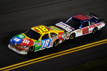 DAYTONA BEACH, FL - FEBRUARY 12:  Kyle Busch, driver of the #18 M&M's Toyota, leads Dale Earnhardt Jr., driver of the #88 National Guard/AMP Energy Chevrolet, during the NASCAR Budweiser Shootout at Daytona International Speedway on February 12, 2011 in D