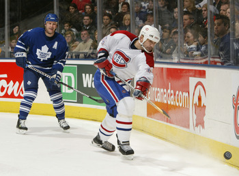 TORONTO - DECEMBER 20:  Sheldon Souray #44 of the Montreal Canadiens shoots the puck up the boards ahead of Gary Roberts #7 of the Toronto Maple Leafs during the game at Air Canada Centre on December 20, 2003 in Toronto, Ontario. The Maple Leafs won the g