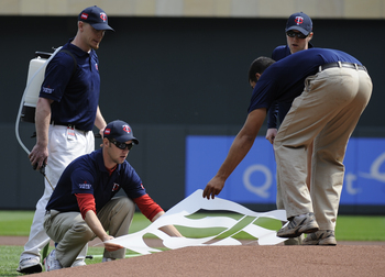 MINNESOTA, MN - APRIL 12: The grounds crew of the Minnesota Twins lay down a logo template on the mound prior to a game between the Minnesota Twins and the Boston Red Sox during the Twins home opener at Target Field on April 12, 2010 in Minneapolis, Minne