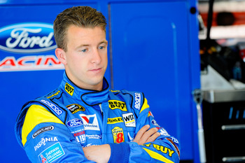 DAYTONA BEACH, FL - FEBRUARY 12:  A.J. Allmendinger, driver of the #43 Best Buy Ford, stands in the garage during practice for the NASCAR Sprint Cup Series Daytona 500 at Daytona International Speedway on February 12, 2011 in Daytona Beach, Florida.  (Pho