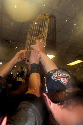 ARLINGTON, TX - NOVEMBER 01:  Players form the San Francisco Giants celebrate with the World Series Championship trophy in the locker room after they won 3-1 against the Texas Rangers in Game Five of the 2010 MLB World Series at Rangers Ballpark in Arling