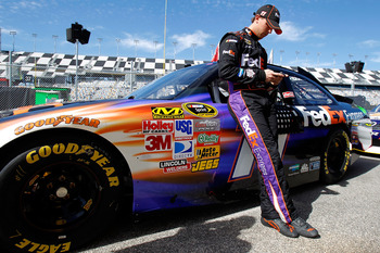 DAYTONA BEACH, FL - FEBRUARY 12:  Denny Hamlin, driver of the #11 FedEx Toyota, leans against his car in the garage area during practice for the NASCAR Sprint Cup Series Daytona 500 at Daytona International Speedway on February 12, 2011 in Daytona Beach,