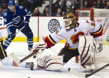 VANCOUVER, CANADA - FEBRUARY 12: Goalie Miikka Kiprusoff #36 of the Calgary Flames breaks up a pass intended for Mikael Samuelsson #26 of the Vancouver Canucks during the second period in NHL action on February 12, 2011 at Rogers Arena in Vancouver, Briti