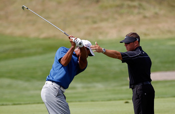 KOHLER, WI - AUGUST 14:  Tiger Woods works with golf instructor Sean Foley on the practice ground prior to the start of the third round of the 92nd PGA Championship on the Straits Course at Whistling Straits on August 14, 2010 in Kohler, Wisconsin.  (Phot