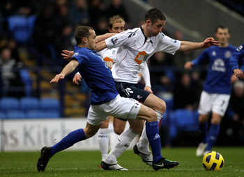BOLTON, ENGLAND - FEBRUARY 13:  John Heitinga of Everton battles for the ball with Gary Cahill of Bolton Wanderers during the Barclays Premier League match between Bolton Wanderers and Everton at the Reebok Stadium on February 13, 2011 in Bolton, England.