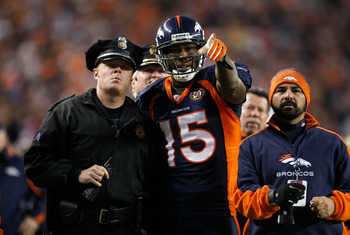 DENVER - DECEMBER 20:  Brandon Marshall #15 of the Denver Broncos points out a disturbance in the crowd to a police officer in the second half against the Oakland Raiders at Invesco Field at Mile High on December 20, 2009 in Denver, Colorado. The Raiders