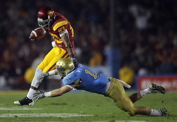 PASADENA, CA - DECEMBER 04:  Wide receiver Ronald Johnson #83 of the USC Trojans breaks a tackle by Sean Westgate #11 of the UCLA Bruins during the first half at the Rose Bowl on December 4, 2010 in Pasadena, California. USC defeated UCLA 28-14.  (Photo b
