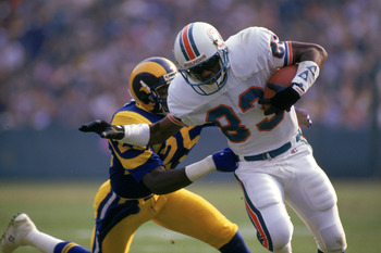 ANAHEIM, CA - DECEMBER 14:  Wide receiver Mark Clayton #83 of the Miami Dolphins tries to break a tackle by defensive back Jerry Gray #25 of the Los Angeles Rams during a game at Anaheim Stadium on December 14, 1986 in Anaheim, California.   The Dolphins