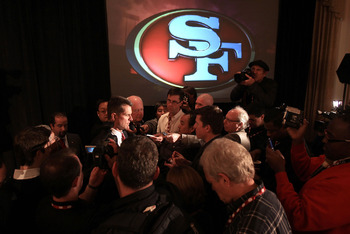 SAN FRANCISCO, CA - JANUARY 07:  Jim Harbaugh is surrounded by media following a press conference where he was introduced as the new San Francisco 49ers head coach at the Palace Hotel on January 7, 2011 in San Francisco, California.  (Photo by Ezra Shaw/G