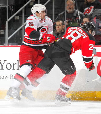 NEWARK, NJ - FEBRUARY 08:   Tuomo Ruutu #15 of the Carolina Hurricanes checks Anton Volchenkkov #28 of the New Jersey Devils during the first period of an NHL hockey game at the Prudential Center on February 8, 2011 in Newark, New Jersey.  (Photo by Paul