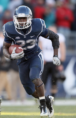 EAST HARTFORD, CT - NOVEMBER 27:  Jordan Todman #23 of the Connecticut Huskies carries the ball around the Cincinnati Bearcats defense on November 27, 2010 at Rentschler Field in East Hartford, Connecticut. The Huskies defeated the Bearcats 38-17.  (Photo