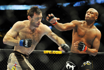 PHILADELPHIA - AUGUST 08:  Anderson Silva (R) throws a right punch to Forrest Griffin during their light heavyweight bout at UFC 101: Declaration at the Wachovia Center on August 8, 2009 in Philadelphia, Pennsylvania.  (Photo by Jon Kopaloff/Getty Images)